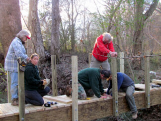 photo of Durham, SC neighbours helping to build a pathway bridge