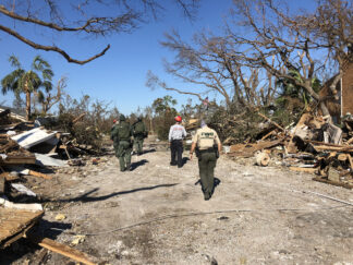 photo of a team from Florida Fish and Wildlife inspect housing destroyed by Hurricane Michael.