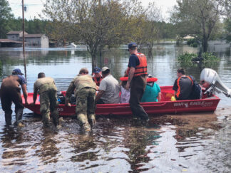photo of rescuers helping flood victims to safety