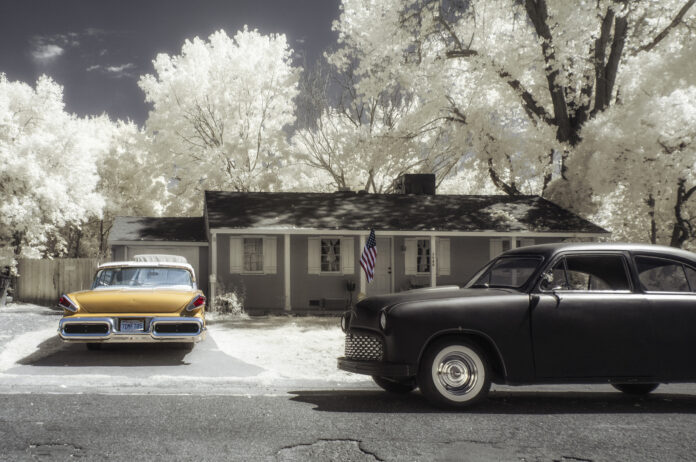 photo of older suburban home with vintage cars