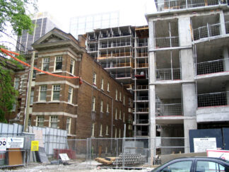 Image of a rental apartment building in front of a condo under construction