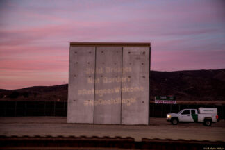 bridges not borders protest projected on proposed wall at US Mexico border