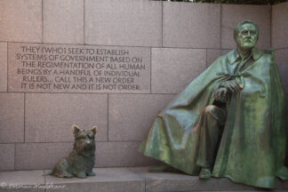 Statue of President Roosevelt and pet dog Fala. Shot includes inscription of FDR quote on systems of government