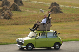 Image of man driving a small car from an armchair mounted on the roof