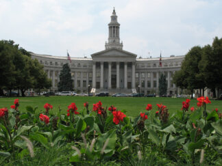 image of denver's city hall with bright red flowers in the foreground