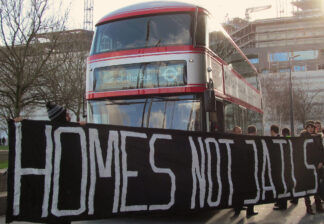 Protest banner with caption homes not jails