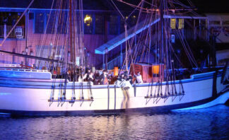 Night shot of tea being poured over the side of the brig Beaver in Boston Harbour