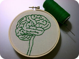 embroidered image of the brain framed by an embroidery hoop