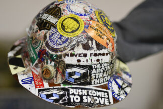 Construction worker's helmet covered with stickers