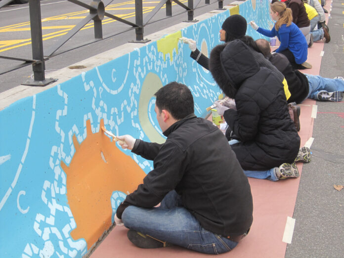 eight people painting a mural of gears on a waist high wall