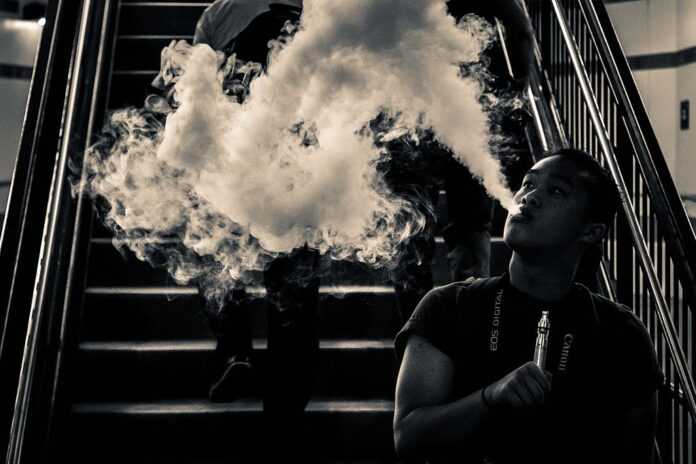person vaping. The 'somke' obscuring people coming down stairs