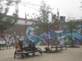 person with possessions on park bench set in front of mural painted on recreation centre