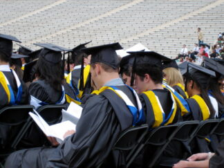 side view of seated people in caps and gowns