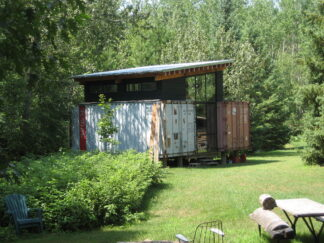house constructed from two shipping containers in a wooded area