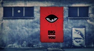 red rectangle framing and eye and the inscription Big Brother is watching you. The image is painted on a gray wall between two windows.