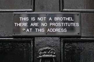 Sign on door, which reads: this is not a brothel. There are no prostitutes at this address.