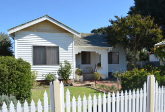white bungalow with picket fence