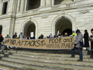 Protesters with banner on the steps of the Minnesota Legislature. The banner text: 2011: No attacks on the poor and working familes.