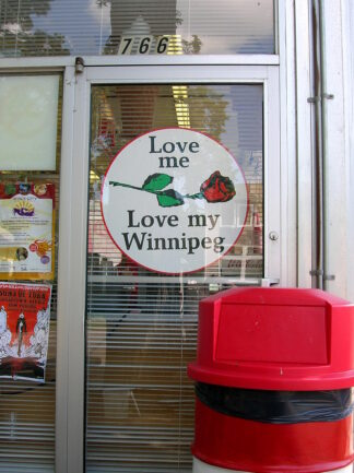 door with sign saying love me love my Winnipeg. There is a red rose on the sign, too.
