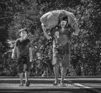 Older man walking along a street, a young boy beside him.