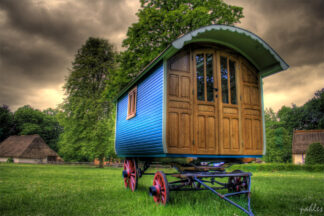 An ornate caravan sitting in a Belgian field