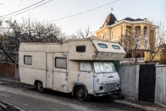 Old camper van parked on a side street, contrasting with decent housing