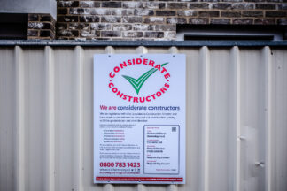 accreditation sign for considerate contractors posted at construction site in Norwich