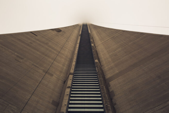 An image of the CN tower, its top lost in the clouds, with a ladder like pattern of its windows climbing upwards