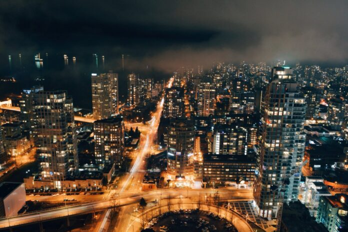 On a foggy night in English Bay, Vancouver, BC, the skies are lit with lights from high rise buildings