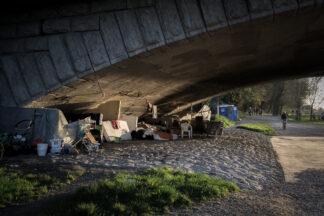 A homeless encampment under a riverside Munich Bridge