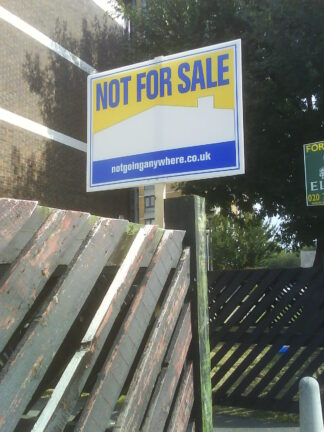 "A ""Not For Sale"" sign in front of a nondescript building"