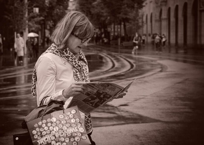 A woman stands in the street reading a newspaper