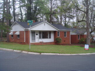 A house in a corner lot in Charlotte North Carolina with a realtor's sign on the lawn