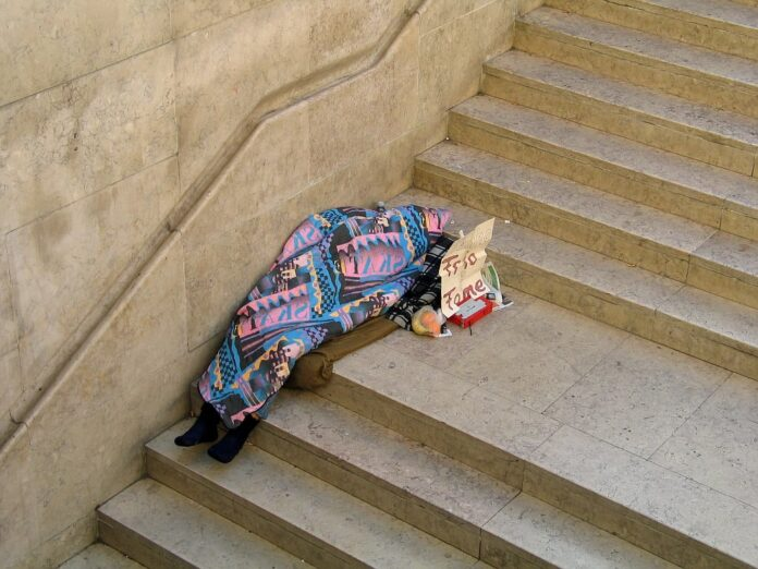 A homeless person sleeps bundled up in a blanket on a Lisbon, Portugal public stairway