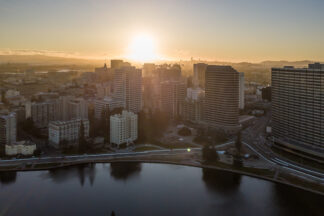 Arial View of Okland with the sun setting behind buildings