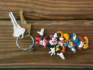 A bunch of keys on a table with little cartoon characters attached