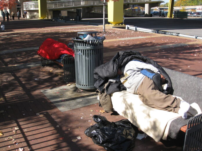 Two Pittsburgh omeless people stretched out under covers on park bench