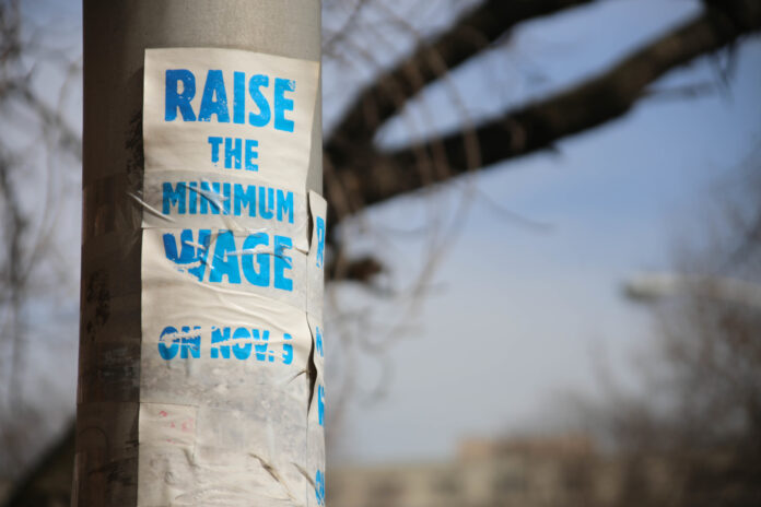 a sign saying 'raise the minimum wage' is taped around a light standard