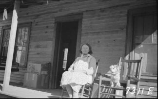 An older woman, a dog on the chair beside her, sits on the front porch of a modest old house