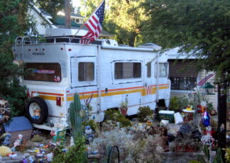 A mobile home sitting in a garden filled with cheery knickknacks