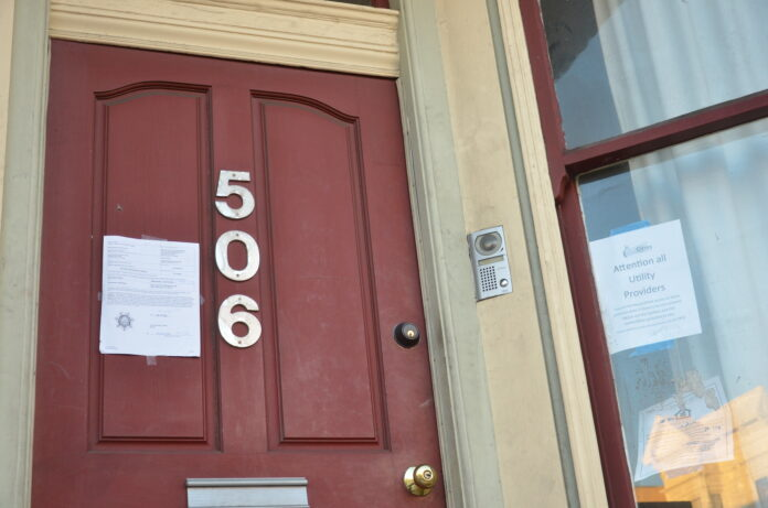 An official white paper notice is taped to a San Francisco house doorway.