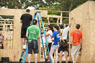 a group of young people erecting plywood walls of a house