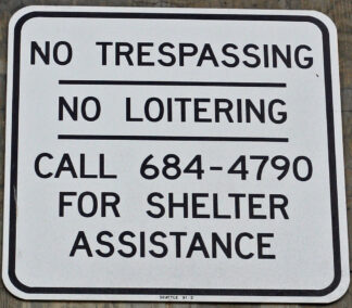 closeup of sign saying no trespassing, no loiter, and giving a phone number of a shelter