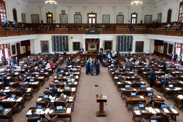 A view of many untidy desks and consulting officials in the senate chamber of the Texas legislature