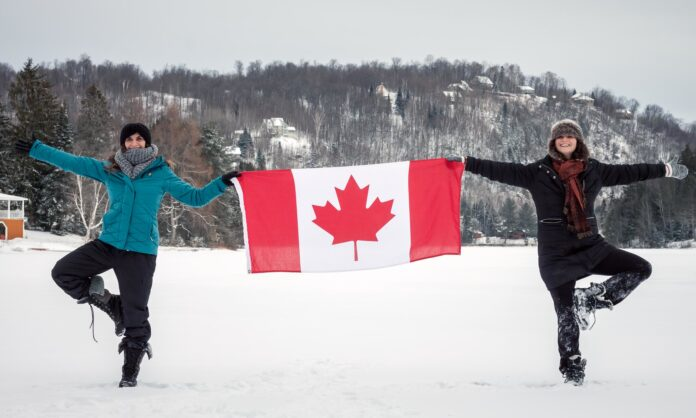 A pair of Canadians holding a Canadian flag above a snow swept field