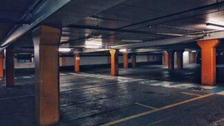 concrete pillars step across a sea of empty asphault