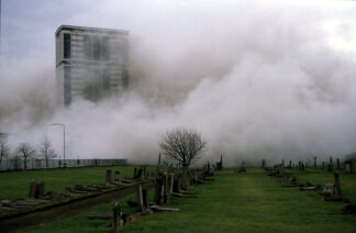 With a graveyard in foreground, a high-rise being demolished is half-hidden in a cloud of dust