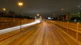 a huge expanse of highway sweeps towards the nighttime lights of distant downtown dallas