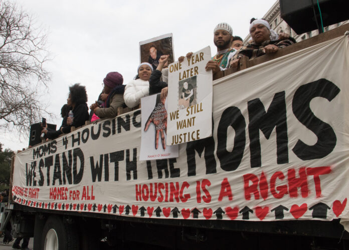people carrying Moms 4 Housing banner
