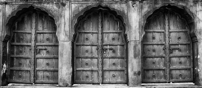 black and white image of three wooden doors, each with a lock